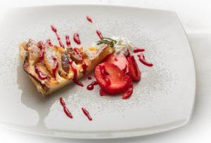 Crostata di frutta servita con fragole fresche e marmellata