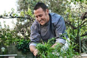 Lo Chef Marco Antonaglia raccoglie erbe aromatiche piantate nel piccolo orto del ristorante La Pitraia, una riserva di sapori e profumi sempre disponibili